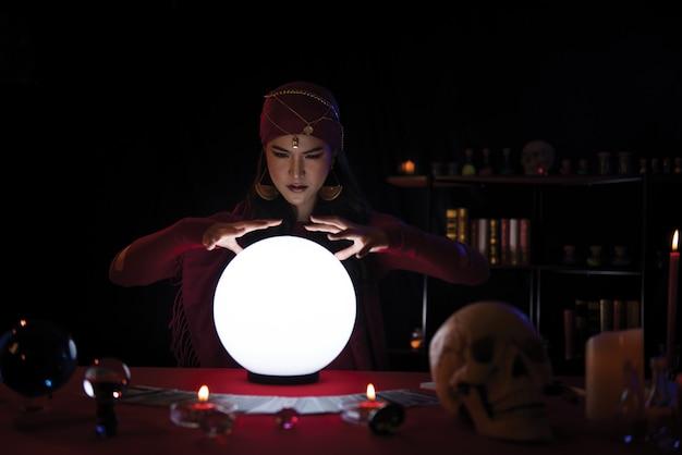 Рассказчик удачи женщины работая с хрустальным шаром с украшением. портрет женщины гадалка. Premium Фотографии