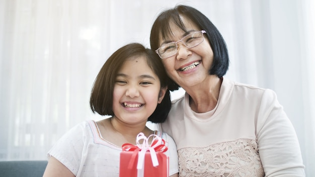 美しいアジアの女の子は、彼女の祖母に宇宙のギフトボックスを与える Premium写真