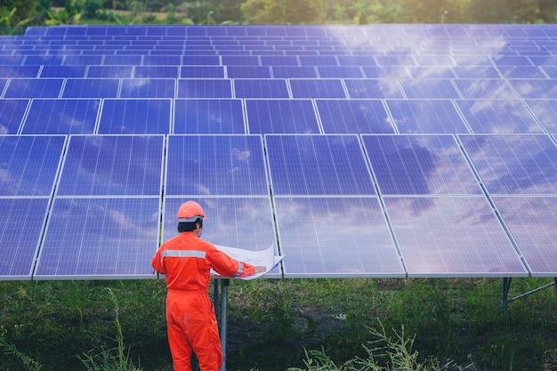 Специалист по электротехнике и приборостроению использует план для планирования и обслуживания электрической системы в области солнечных батарей Premium Фотографии
