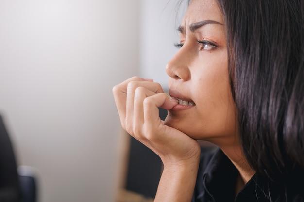 Слабонервная коммерсантка сдерживая ее ногти с эмоцией беспокойства в офисе. Premium Фотографии