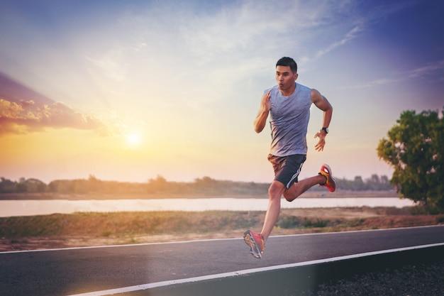 道路に全力疾走を走っている人のシルエット。屋外トレーニング中にフィットする男性フィットネスランナー Premium写真