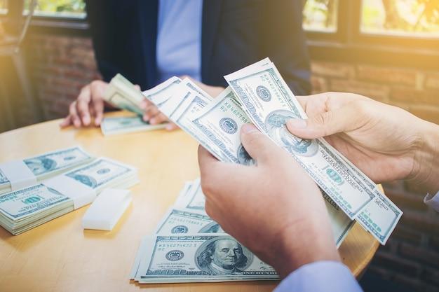 Руки банкира, подсчитывающие долларовые банкноты на столе Premium Фотографии