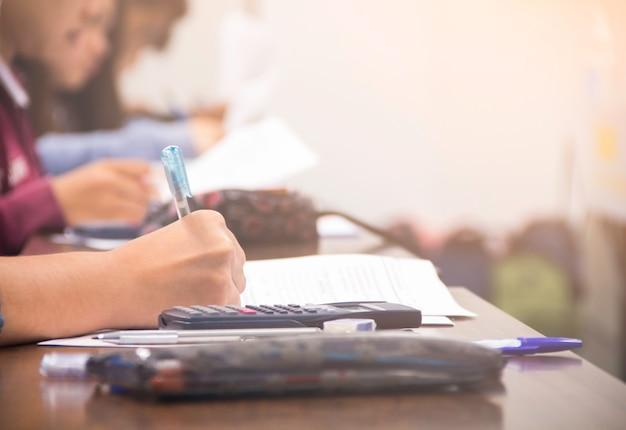 試験/研究またはクイズを行うペンライティング/電卓を保持している大学生の手 Premium写真