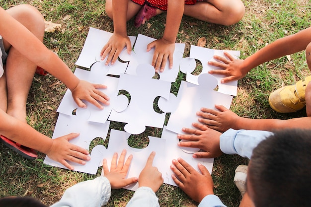 Группа детей с разными этническими особенностями объединена, чтобы вместе поиграть в пазлы и головоломки на детской площадке. концепция совместной работы, сотрудничества, обучения и образования. Premium Фотографии