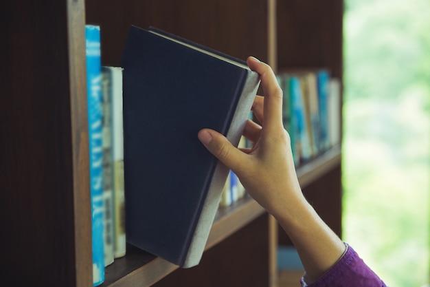 手は図書館の本棚で本を選んだ。学校コンセプトへの教育 Premium写真