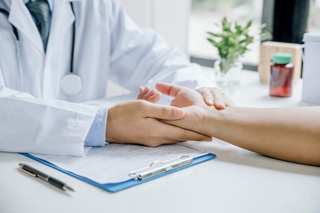 Врач проверяет артериальное давление пациента в медицинском кабинете Premium Фотографии
