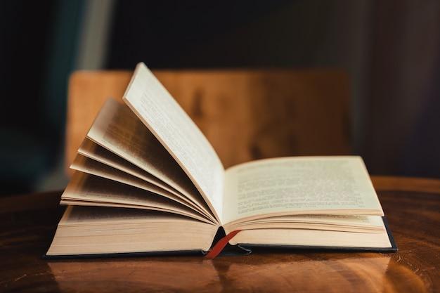 窓の光と木製のテーブルに朝の献身のための聖書を開く Premium写真