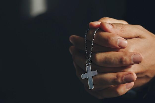 クロスネックレスを保持している手を閉じます。より良い人生を願って神の祝福を祈ります Premium写真
