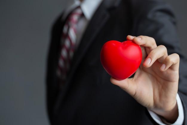 Бизнесмен держит красное сердце Premium Фотографии
