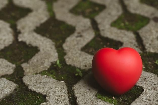 赤いハートがコンクリートの床に置かれています Premium写真