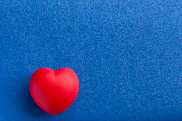 Красное сердце на синем столе Premium Фотографии