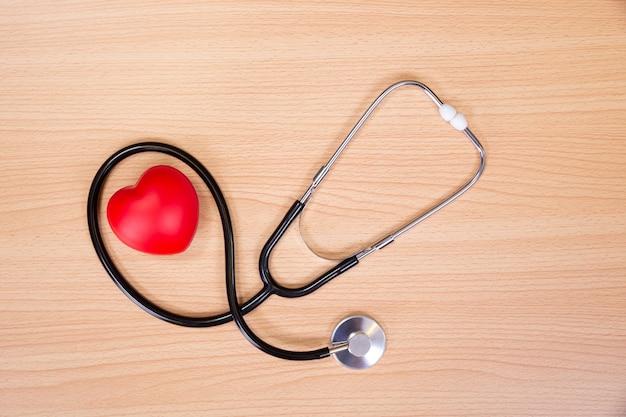 赤いハートと木製のテーブルの聴診器。ハートビートを聞くための医師ツール。医療コンセプト。 Premium写真