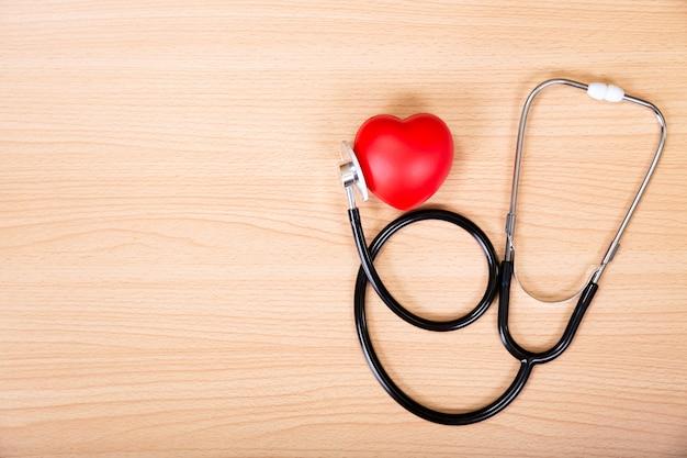 Красное сердце и стетоскоп на деревянном столе. Premium Фотографии