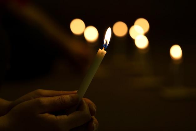 暗闇の中でキャンドルの徹夜を照明の手を閉じる Premium写真