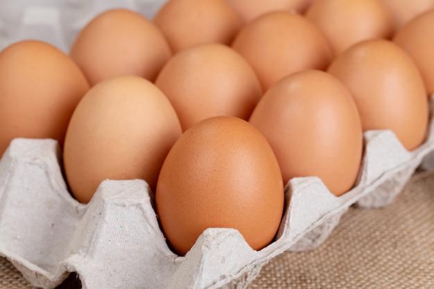 卵、鶏の卵。布の上の段ボール箱に卵。 Premium写真