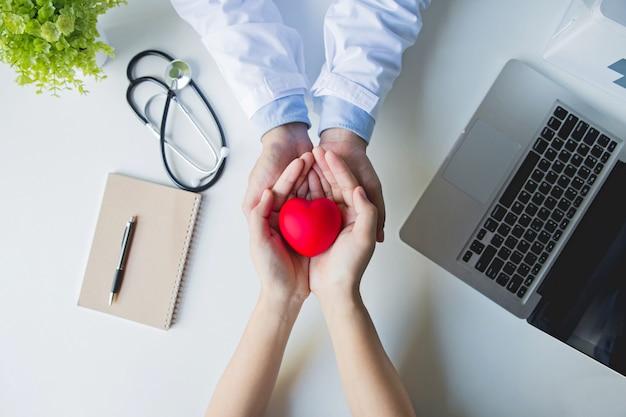 Вид сверху . руки доктора и пациента держа красное сердце на белом столе Premium Фотографии