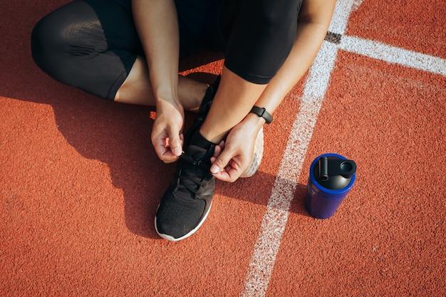 Человек спортсмена сидя на шнурке на стадионе. старт Premium Фотографии