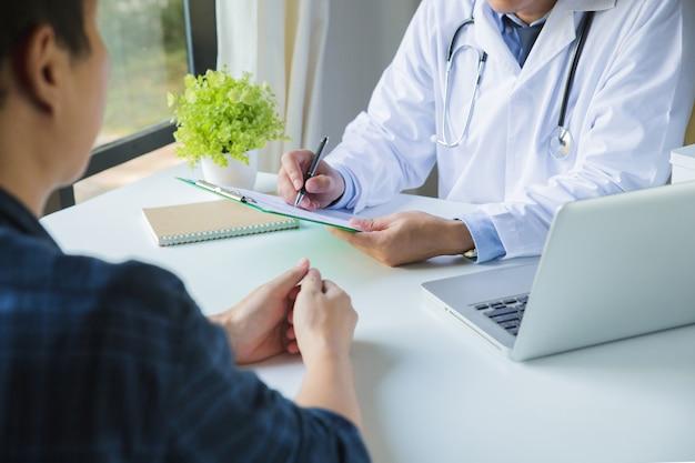 クリップボードを使用して、若い男性の薬の病歴を記入する医師と、診療所での身体検査の結果について話し合う患者 Premium写真