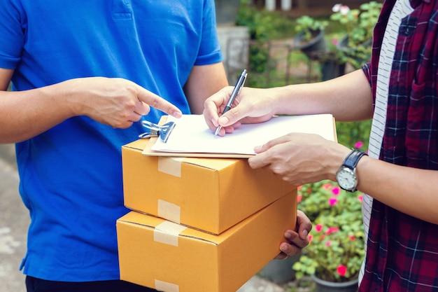 Подписание, чтобы получить пакет. молодой доставщик держит картонную коробку, а красивый молодой человек ставит подпись в буфер обмена Premium Фотографии