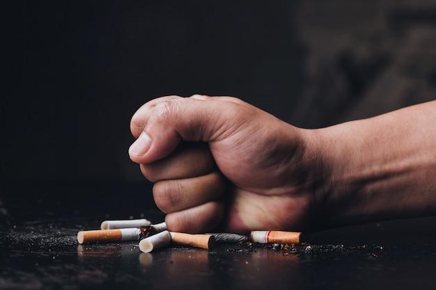 Сигареты мужской руки разрушая на черной предпосылке бросьте курить. всемирный день без табака Premium Фотографии