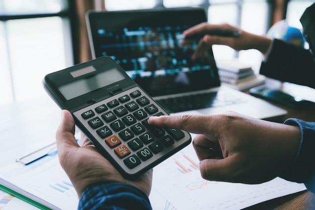 認識できない金融用途の計算機を持っている若いビジネス人の手は、オフィスでのコストについて計算します。 Premium写真
