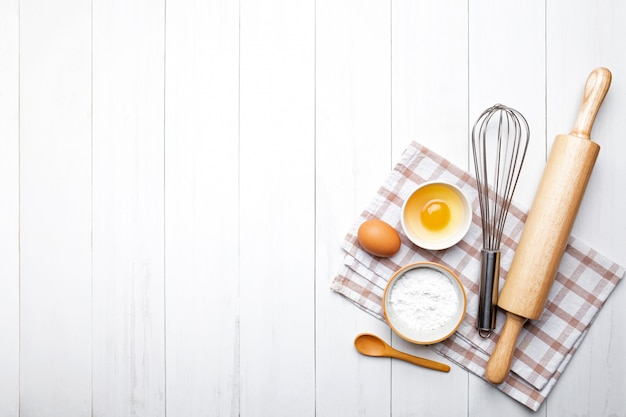 パン屋さんの材料。小麦の穂と小麦粉、卵、麺棒、卵泡立て器のボウル Premium写真