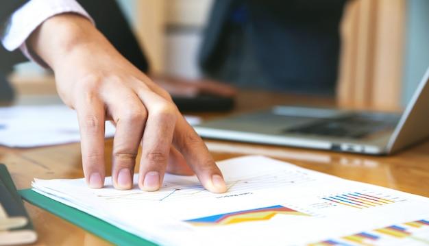 Закройте вверх руки сотрудника дела указывая на деловой документ во время обсуждения на встречу. деловые люди мозгового штурма на рабочий стол. Premium Фотографии