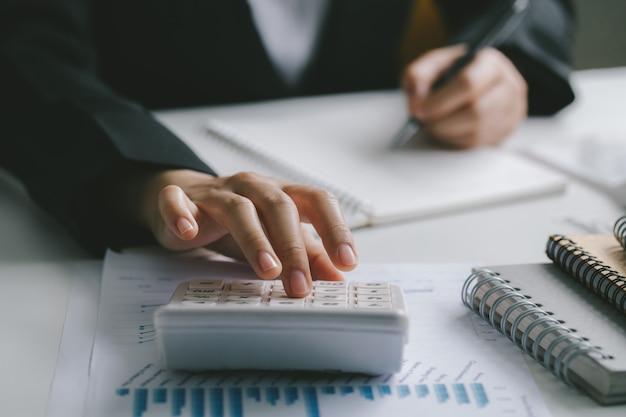 電卓を使用して書く女性の手を閉じると財務会計についての計算でメモを作成します。財務会計の概念 Premium写真