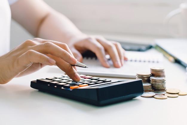 Молодая женщина, расчет ежемесячных расходов на жилье, налоги, остаток на банковском счете и оплата счетов кредитной карты. Premium Фотографии