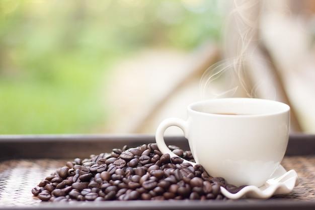 白いコーヒーのマグカップとコーヒー豆は、背景をぼかし、ホットコーヒーのカップは、コーヒー豆の横に配置されます。 Premium写真