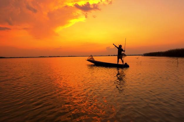夕日とシルエットの漁師 Premium写真