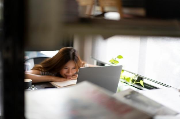 アジアビジネスの女の子がカフェでラップトップコンピューターでの作業を開始 Premium写真