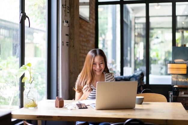 アジアビジネスの女の子幸せとカフェでラップトップコンピューターでの作業を開始 Premium写真