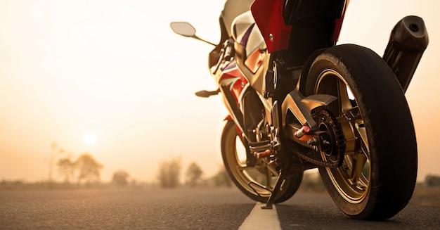 Стоянка для мотоциклов на дороге справа и закат Premium Фотографии