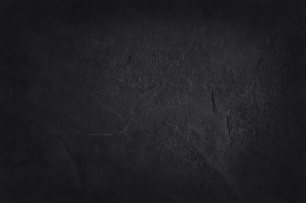 Темно-серая черная текстура шифера, предпосылка естественной черной каменной стены. Premium Фотографии