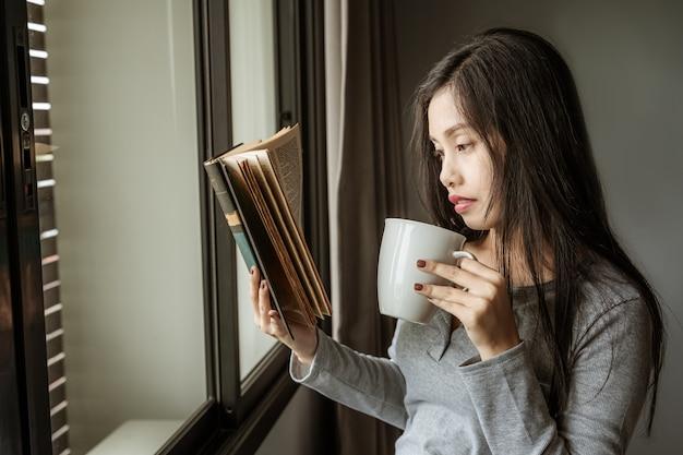 Азиатские студентки стоят, чтобы читать книги у окна Premium Фотографии