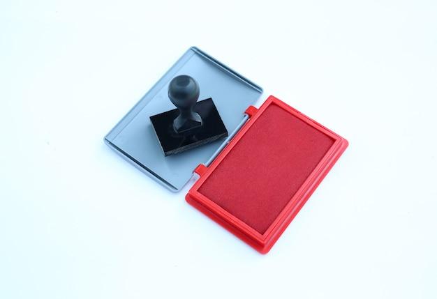白い背景にゴム印と赤インクカートリッジ。 Premium写真