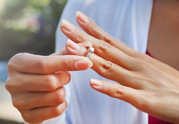 女性は結婚指輪を離陸しています Premium写真
