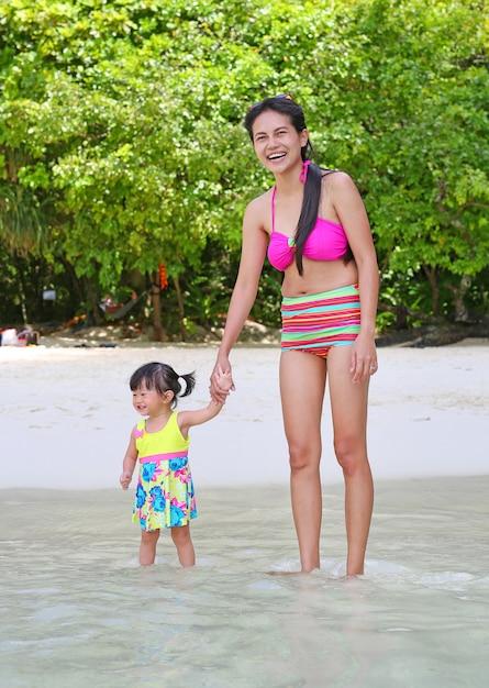 幸せな家族 - 海のビーチの母親と小さな赤ちゃんの娘。 Premium写真