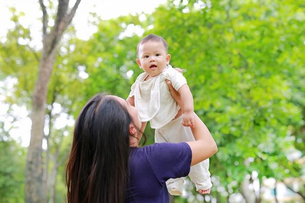 Азиатская мать бросает своего ребенка на руках в саду. Premium Фотографии