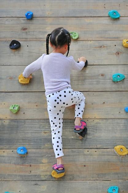 屋外の遊び場の木製の壁に無料で登山しようとしている小さな子女の子 Premium写真
