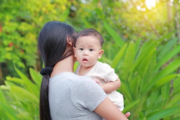 Азиатская мать нося ее младенческий ребёнок в зеленом саде. Premium Фотографии