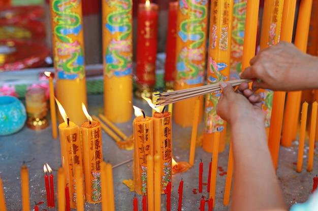 人々は中国の旧正月の日に神のために燃える香を尊重することを祈ります。 Premium写真