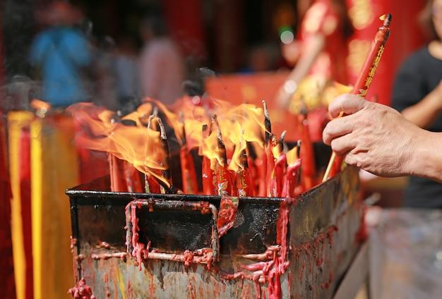 人々は中国の新年の日に神のために燃えているろうそくに敬意を表します。 Premium写真