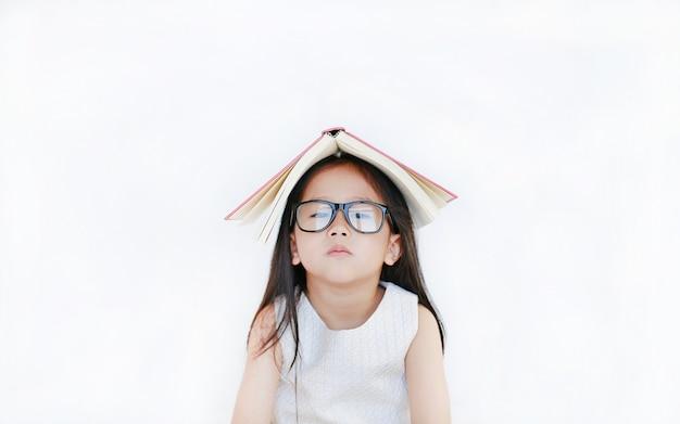 小さなアジアの女の子の肖像画は彼女の頭の上のハードカバーの本を置き、白い背景の上にカメラを探しています。 Premium写真