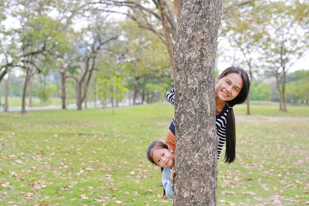 Азиатские мама и маленькая девочка прячут тело за деревом в саду. Premium Фотографии