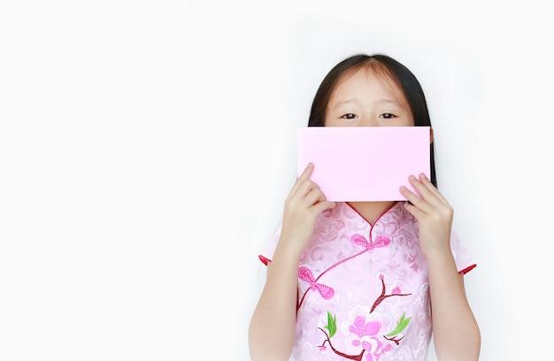 彼女の口に中国の旧正月ピンク封筒パケットを保持している小さなアジアの女の子。 Premium写真