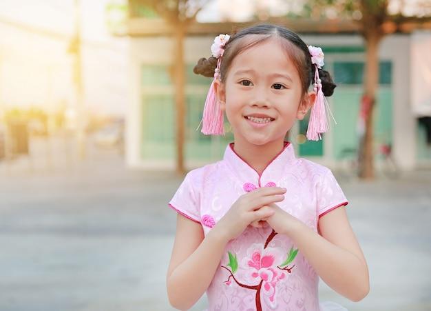 中国の新年のジェスチャーお祝いの挨拶幸せな小さなアジアの女の子。 Premium写真
