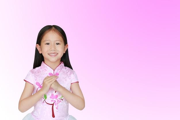 ジェスチャーのお祝いの挨拶とピンクの伝統的な中国のドレスを着て幸せの小さなアジア子供女の子 Premium写真