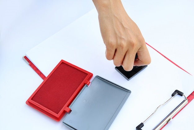 白い紙の上の赤いインクパッド(ボックス)とゴムスタンパを使用して手。 Premium写真